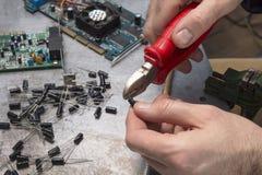 Um trabalhador eletrônico do serviço corta a ponta do capacitor com alicates Foto de Stock