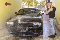 Um trabalhador enxágua lentamente a parte dianteira de um carro preto na lavagem de carros imagens de stock royalty free