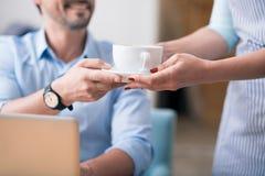 Um trabalhador fêmea do café que dá o café imagem de stock royalty free