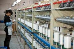 Um trabalhador fêmea que trabalha na oficina de matéria têxtil Imagens de Stock Royalty Free