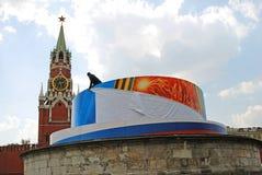Um trabalhador fixa uma bandeira do feriado no quadrado vermelho em Moscou. Imagens de Stock Royalty Free