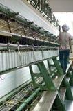 Um trabalhador fêmea que trabalha na oficina de matéria têxtil Imagem de Stock