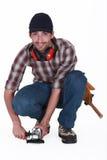 Um trabalhador manual que usa uma máquina de lixar fotografia de stock