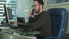 Um trabalhador masculino considerável em um escritório do centro de atendimento que fala em um telefone vídeos de arquivo