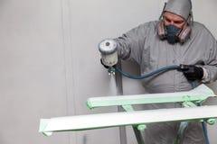 Um trabalhador masculino pinta com uma arma de pulverizador um a parte do corpo de carro na prata após a danificação em um aciden imagens de stock royalty free