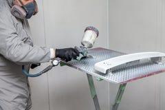 Um trabalhador masculino pinta com uma arma de pulverizador um a parte do corpo de carro na prata após a danificação em um aciden fotos de stock