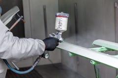 Um trabalhador masculino pinta com uma arma de pulverizador um a parte do corpo de carro na prata após a danificação em um aciden foto de stock