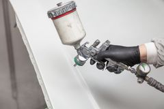 Um trabalhador masculino pinta com uma arma de pulverizador um a parte do corpo de carro na prata após a danificação em um aciden fotografia de stock