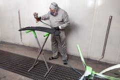 Um trabalhador masculino pinta com uma arma de pulverizador um a parte do corpo de carro na prata após a danificação em um aciden fotografia de stock royalty free