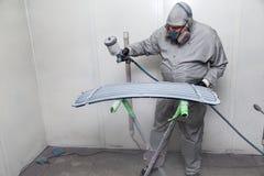 Um trabalhador masculino pinta com uma arma de pulverizador um a parte do corpo de carro na prata após a danificação em um aciden imagem de stock royalty free