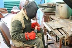 Um trabalhador masculino um soldador em uma máscara protetora solda uma tubulação do metal em uma estação da soldadura em uma ofi foto de stock