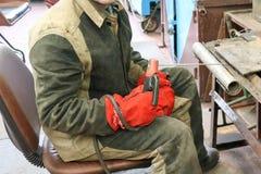 Um trabalhador masculino um soldador em uma máscara protetora solda uma tubulação do metal em uma estação da soldadura em uma ofi imagens de stock