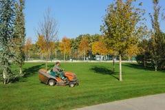 Um trabalhador no minitractor de Husqvarna recolhe as folhas caídas nos gramados no parque novo Krasnodar da cidade perto do está imagem de stock