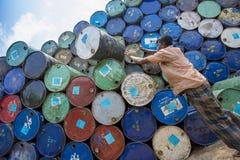 Um trabalhador organiza tambores em áreas de Sadarghat dos rios de Karnafuli, Chittagong, Bangladesh Imagem de Stock Royalty Free