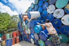 Um trabalhador organiza tambores em áreas de Sadarghat dos rios de Karnafuli, Chittagong, Bangladesh Fotos de Stock