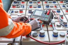 Um trabalhador a pouca distância do mar da plataforma petrolífera usou o medidor à tensão de medição das baterias na plataforma d imagem de stock