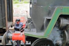 Um trabalhador que ajusta os acoplamentos no trem Railway do vapor de Swanage, ilha de Purbeck, Dorset fotografia de stock