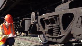 Um trabalhador railway da jovem mulher verifica a unidade do engate do vagão do frete video estoque