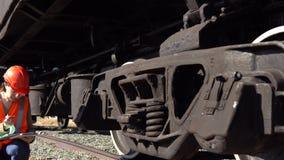 Um trabalhador railway da jovem mulher verifica a unidade do engate do vagão do frete filme