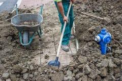 Um trabalhador trabalha com pá a sujeira em um carrinho de mão 2 imagem de stock