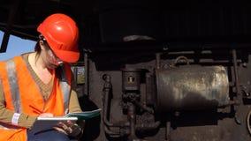 Um trabalhador verifica do sistema hidráulico de uma máquina escavadora da carreira video estoque