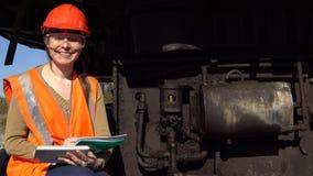 Um trabalhador verifica do sistema hidráulico de uma máquina escavadora da carreira filme