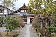 Um trajeto alinhado com arbustos conduz à entrada de um templo em Kyoto (Japão) Foto de Stock Royalty Free