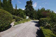 Um trajeto alinhou com placas em um parque pitoresco com os grandes arbustos luxúrias e as árvores verdes Um lugar bonito para o  Imagem de Stock