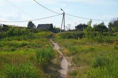 Um trajeto através de um campo com grama verde a uma vila velha Fotografia de Stock