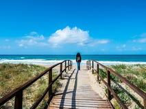 Um trajeto de madeira que conduz à praia, no fundo uma mulher que anda para o mar, na natureza selvagem fotografia de stock royalty free