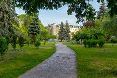 Um trajeto feito da pedra pavimentada em um parque e em um pessoa verdes que descansam em um banco Fotos de Stock Royalty Free