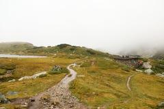 Um trajeto longo que conduz às montanhas no fundo de uma casa pequena foto de stock