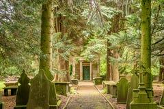Um trajeto que conduz através das lápides e das árvores ao túmulo imagens de stock