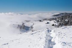 Um trajeto a uma vila pequena através da inclinação nevado na parte superior da montanha imagens de stock royalty free