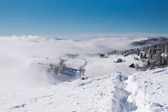 Um trajeto a uma vila pequena através da inclinação nevado na parte superior da montanha imagem de stock
