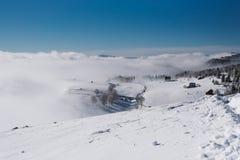 Um trajeto a uma vila pequena através da inclinação nevado na parte superior da montanha fotos de stock