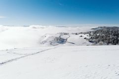 Um trajeto a uma vila pequena através da inclinação nevado na parte superior da montanha foto de stock royalty free