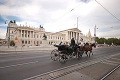 Um transporte puxado por cavalos chamou passagens do fiaker pela construção austríaca do parlamento imagem de stock royalty free