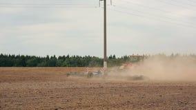Um trator agrícola que ara um campo antes de semear, movendo-se da esquerda para a direita Uma floresta no fundo video estoque