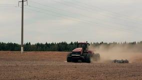 Um trator agrícola que ara um campo antes de semear, movendo-se para a câmera Uma floresta no fundo, poeira do solo filme