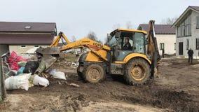 Um trator amarelo grande armazena o lixo da construção em uma pilha usando uma cubeta video estoque