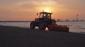 Um trator limpa a areia da praia no nascer do sol filme