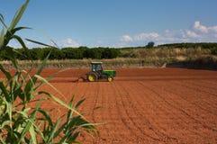 Um trator que trabalha na paisagem da exploração agrícola foto de stock