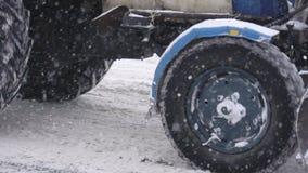 Um trator velho para passeios da remoção de neve a uma cidade do inverno, queda de neve, movimento lento filme