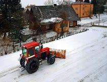 Um trator vermelho cancela a estrada da neve Limpeza do inverno da rua SERVIÇO COMUNITÁRIO Tempo Vila do inverno snowblower Imagens de Stock Royalty Free