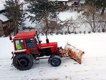 Um trator vermelho cancela a estrada da neve Limpeza do inverno da rua SERVIÇO COMUNITÁRIO Tempo Vila do inverno snowblower Fotos de Stock