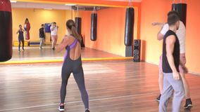 Um treinador individual das artes marciais ensina um homem e um encaixotamento da menina e uma autodefesa, desportista vídeos de arquivo