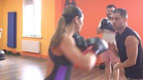 Um treinador individual do encaixotamento e das artes marciais ensina as habilidades da autodefesa da menina e as técnicas, sport vídeos de arquivo