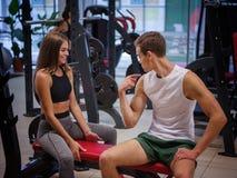 Um treinador que mostra resultados de seu treinamento a uma jovem mulher em um fundo colorido do gym Conceito saudável do estilo  imagens de stock royalty free