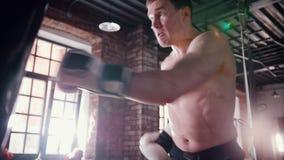 Um treinamento agressivo do pugilista do homem com um saco de perfuração no gym video estoque